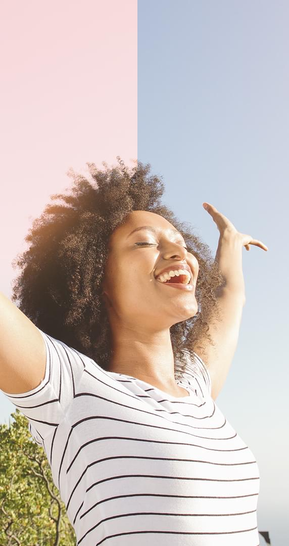 Woman with eyes closed and arms raised in happiness